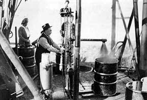 Catching gushing oil in a steel barrel, Norman Wells, NWT, Canada, in 1922.
